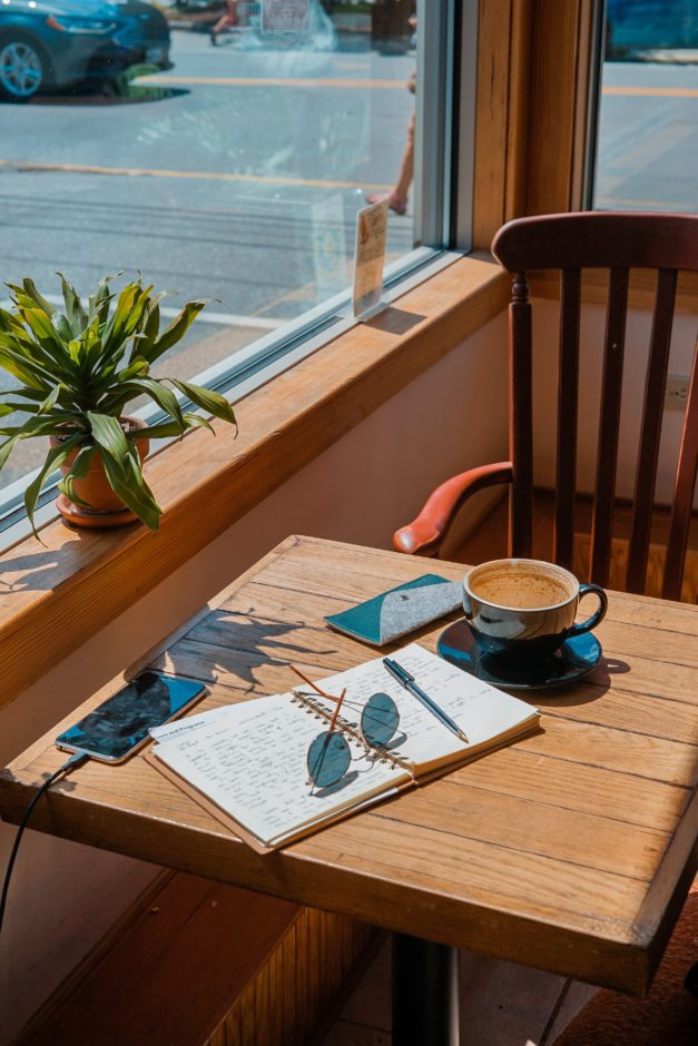 Table by window with open book and coff